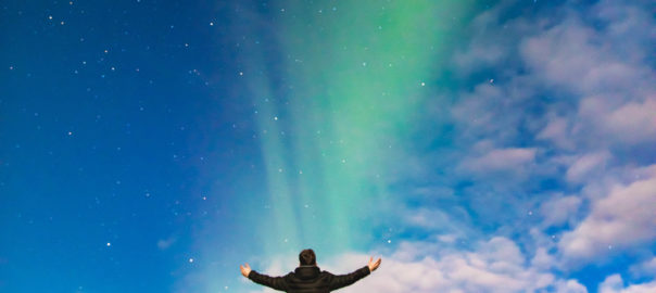 man and aurora borealis